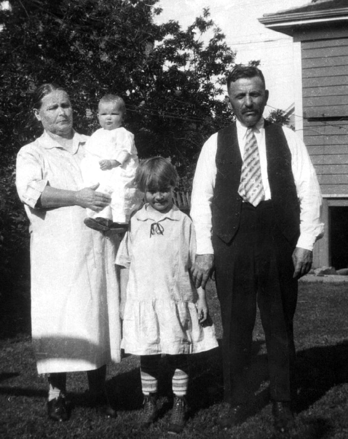 Anna Schmidt holding her granddaughter, Donna Hawes, the daughter of Mary (nee Schmidt) Hawes. Esther Smith stands with her father Johannes Schmidt. The photograph was taken in Portland about 1927.